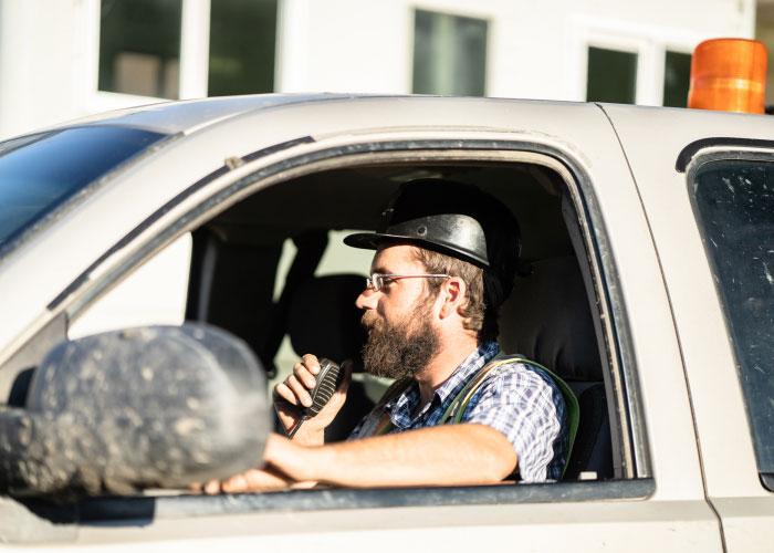 Preston Contractors Employee Using Walkie Talkie Inside A Car